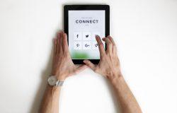 Man holding tablet showing social media platforms